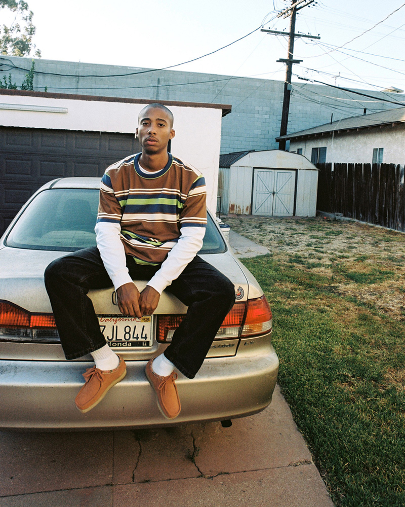 METCHA - Clarks' suede craftsmanship - guy wearing Clarks' suede Wallabees sitting on a car.